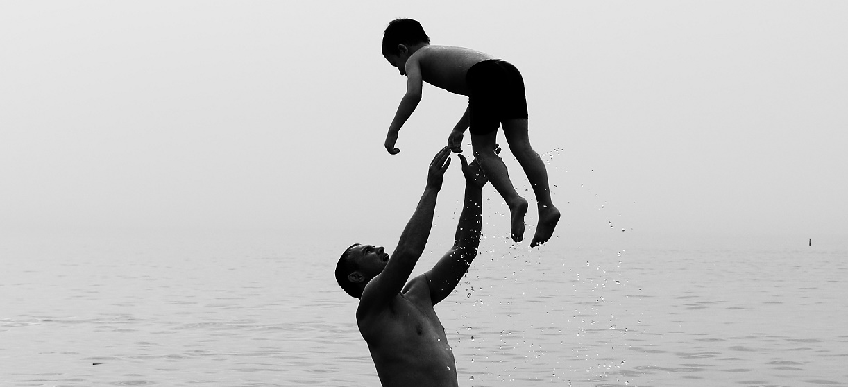 man throwing son in water